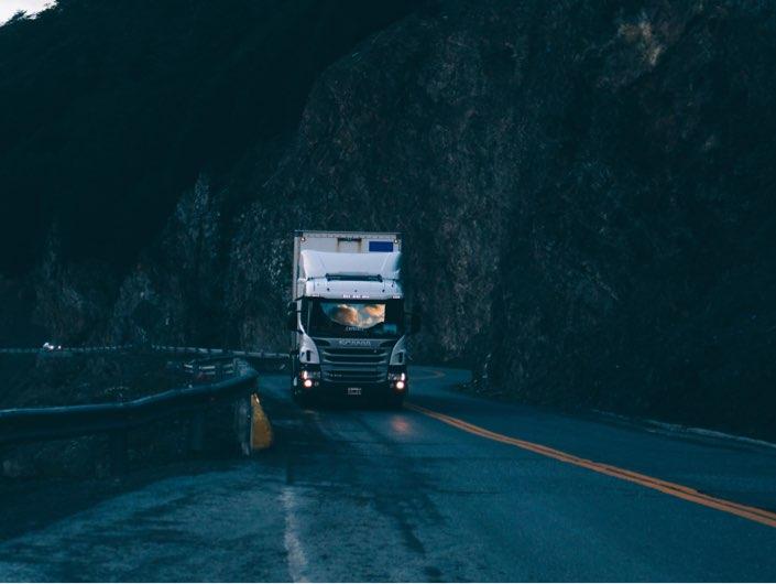Lastbil kör på vägen med berg på sidan